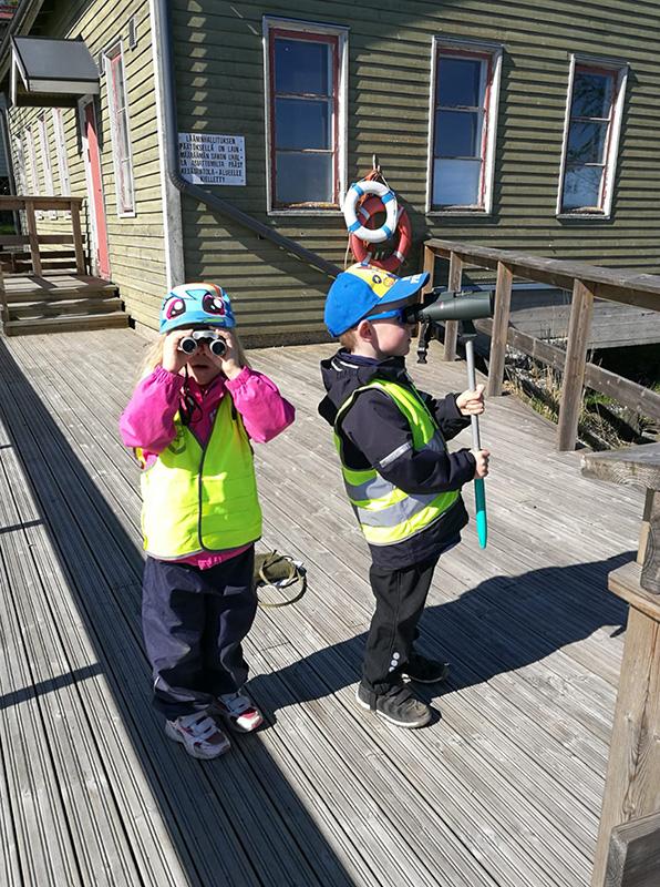 Kaksi lasta kiikaroi terassilla. Kuva: Katariina Boman.
