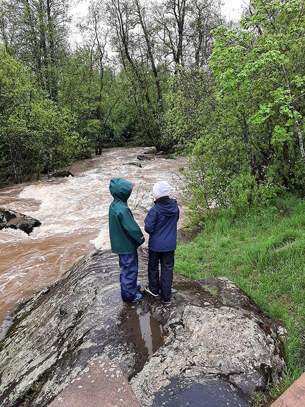 Kaksi lasta selin joen rantakalliolla. Kuva: Maria Kotilainen.
